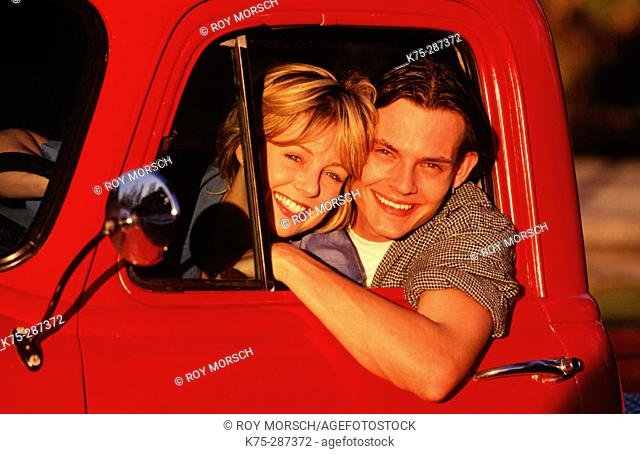 Happy couple in red pick-up truck