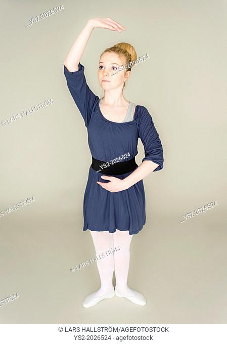 Young blond female teenager in ballet dress standing in dance pose
