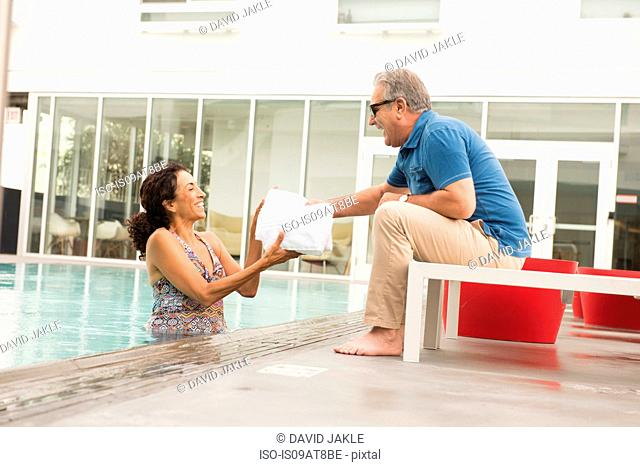 Senior man handing towel to wife from poolside
