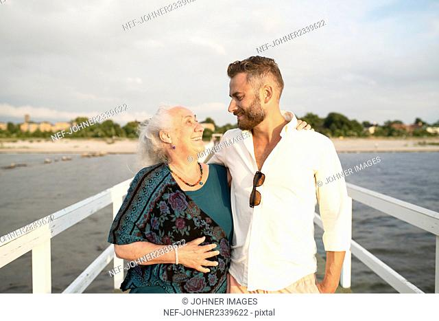 Man with senior mother embracing on pier