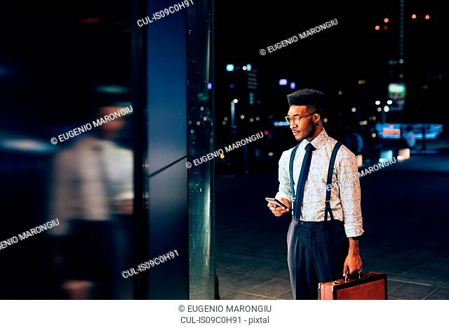 Businessman looking into window of shop
