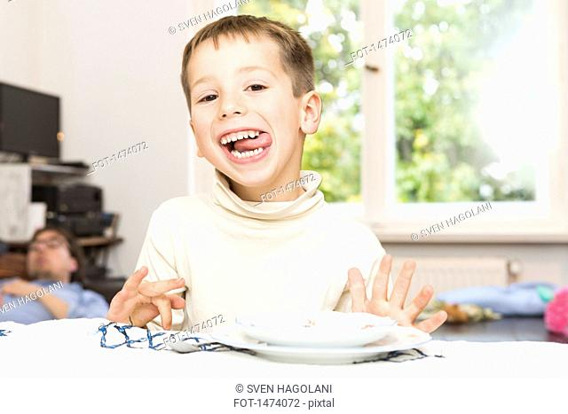 Portrait of cute boy sticking out tongue at table