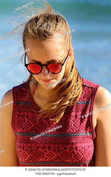 young woman enjoying vacation walking on the beach, here free of crowds Porto de Mos beach, Lagos, Algarve, Portugal, Europe