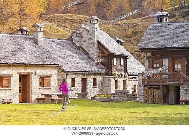 Tourist among Crampiolo's houses, Alpe Veglia and Alpe Devero Natural Park, Baceno, Verbano Cusio Ossola province, Piedmont, Italy