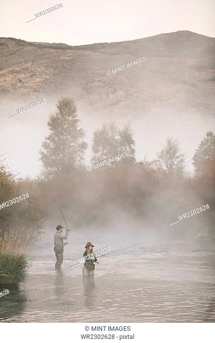 A couple, a man and woman standing in mid stream fly fishing in a river
