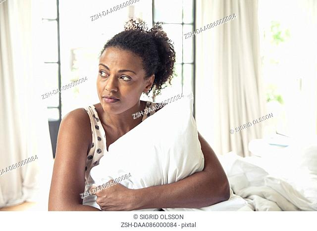 Woman hugging pillow on bed, portrait