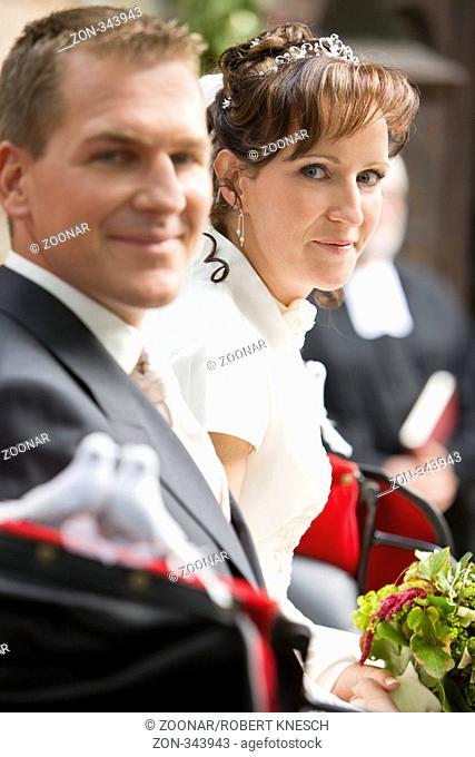 Braut und Bräutigam sitzen glücklich in einer Kutsche
