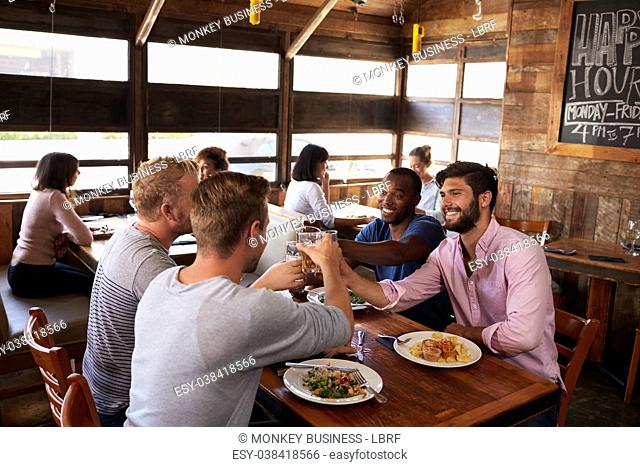 Four male friends making a toast at a table in a restaurant