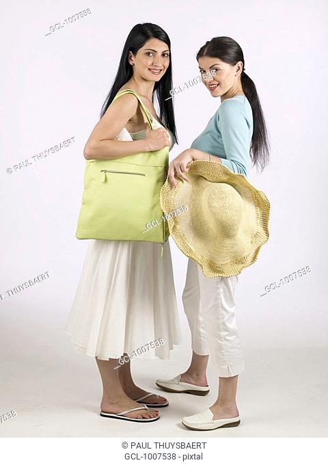 Two women holding sunhat and green handbag