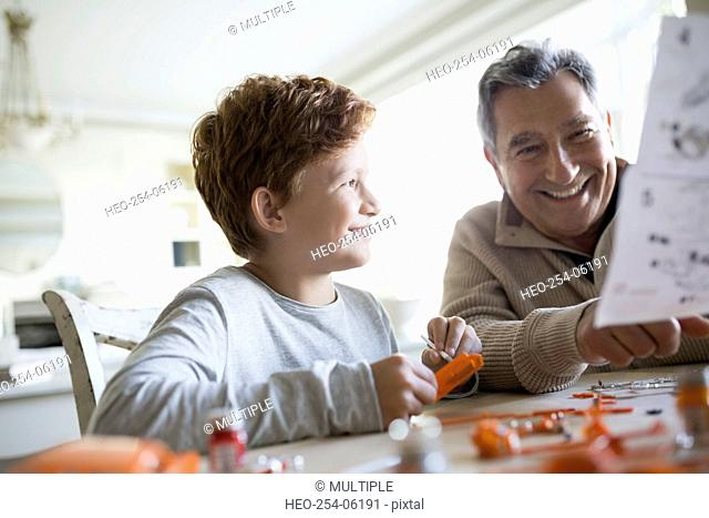 Smiling grandfather and grandson assembling model cars