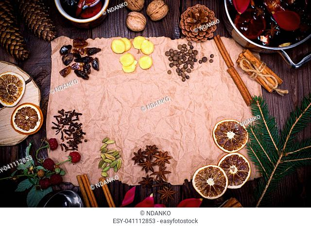 Ingredients and spices for cooking homemade alcohol mulled wine on brown kraft paper, empty space in the middle