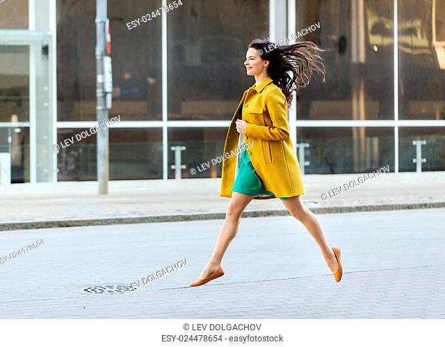 fashion and people concept - happy young woman or teenage girl running and jumping high on city street