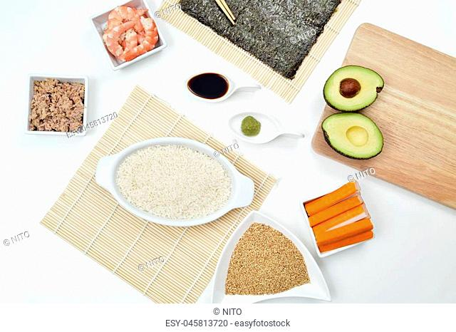 high-angle shot of a table with some of the ingredients and tools to prepare sushi, such as bamboo mats, sushi rice, tuna, avocado, shrimps or nori sheets