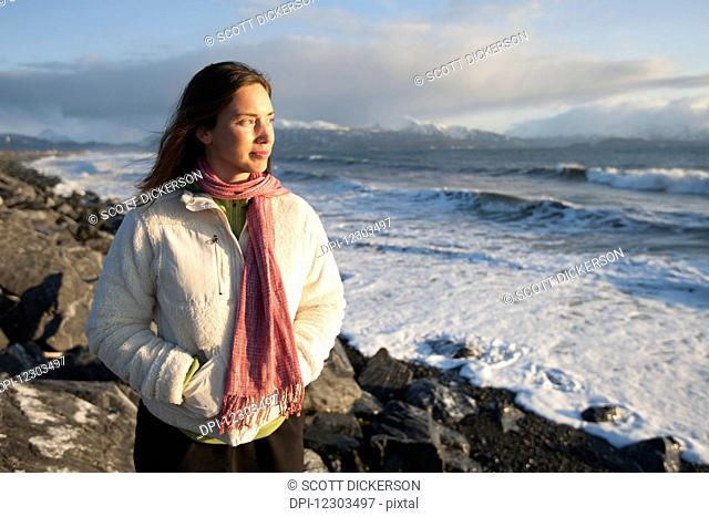 Woman standing along the rocky shoreline of Homer Spit at sunset in winter, Southcentral Alaska