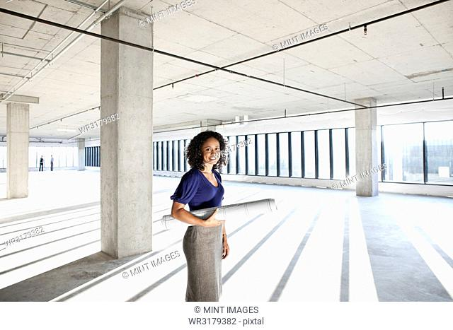 Black woman architect standing in a large empty raw office space