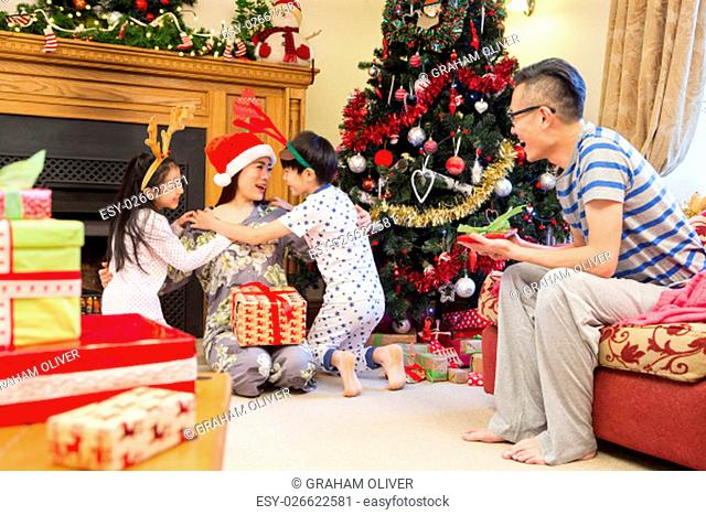 Chinese family enjoying Christmas in their home. The children are cuddling their Mother who is sitting by the Christmas tree with presents