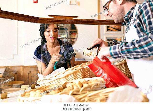 Customer in bakery pointing to baked goods, worker placing goods in bag