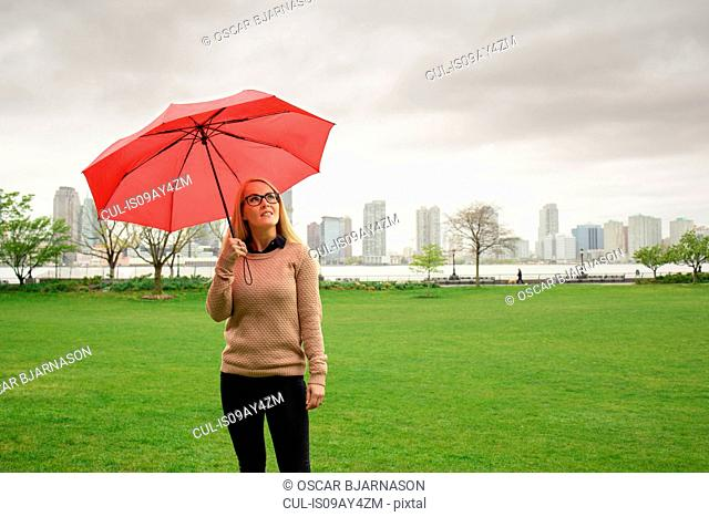 Female tourist with red umbrella in East River park, New York, USA