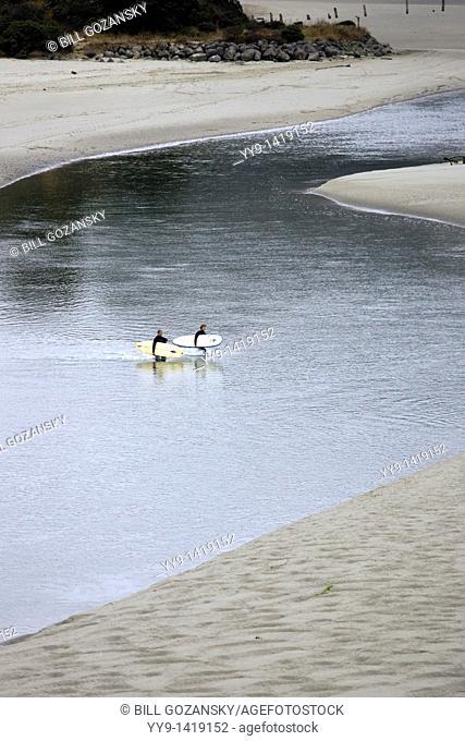 Surfers crossing tidal river - Mendocino, California