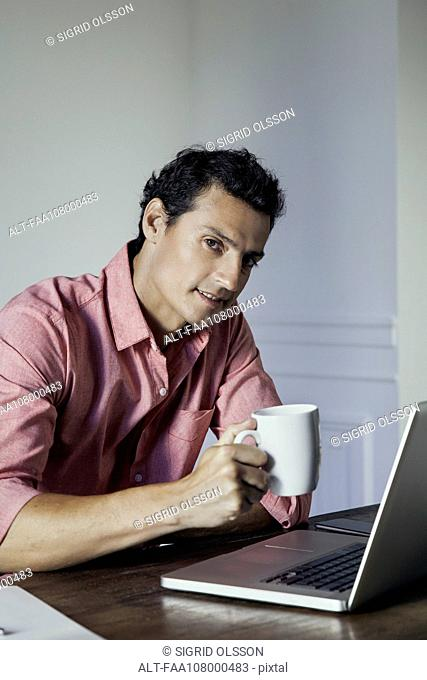 Man relaxing with laptop computer and cup of coffee