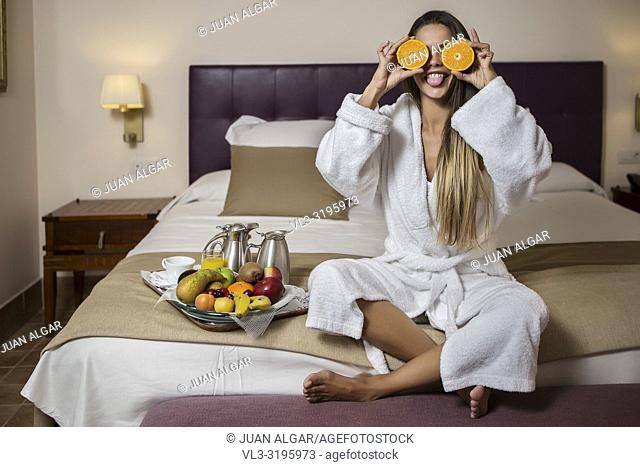 Young pretty woman in hotel morning gown sitting on bed with slices of orange near eyes and showing tongue with plate of fresh fruits placed near