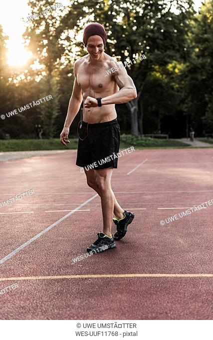Shirtless man on sports field looking at wearable