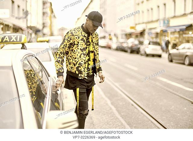 young stylish man with hands on doorknob of taxi, opening car door, at city street, wearing trendy fashion clothes, in Munich, Germany