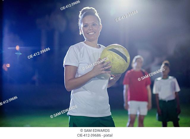 Portrait smiling, confident young female soccer player holding soccer ball on field at night