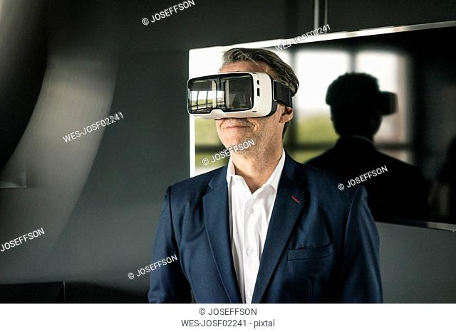 Mature businessman wearing VR glasses in office