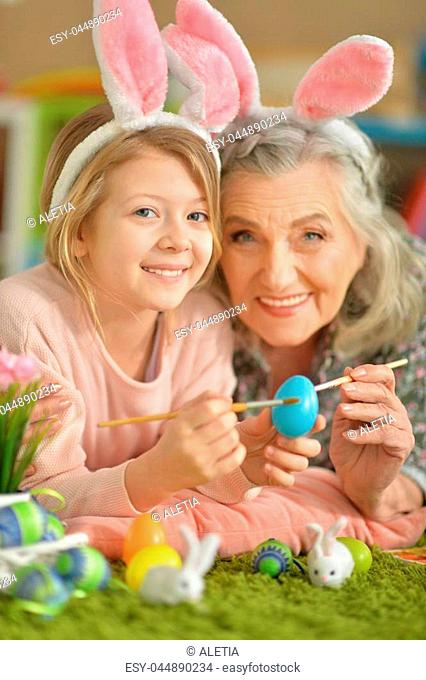 Portrait of grandmother and granddaughter paint Easter eggs