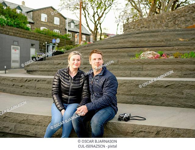 Young couple sitting on steps, looking at view, Vagsbotnur, Torshavn, Faroe Islands