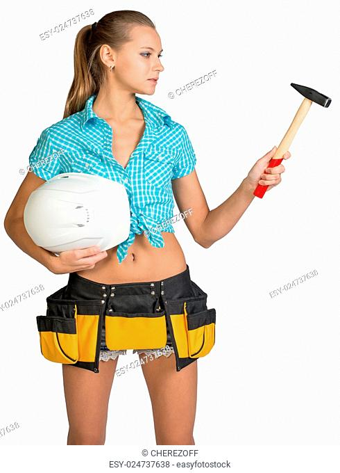 Pretty girl in shorts, shirt and tool belt holding white hard hat and hammer. Isolated over white background