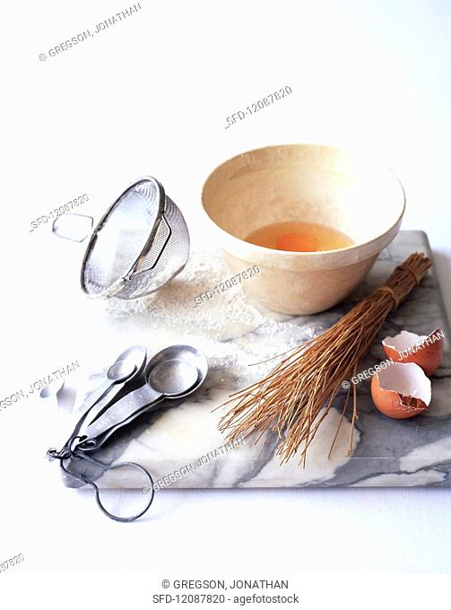 A whisked egg and assorted baking utensils