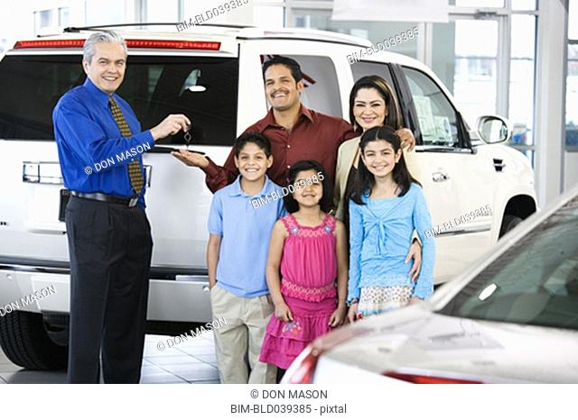 Hispanic car salesman handing car keys to family