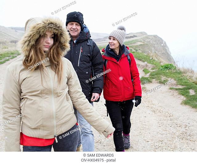 Family in warm clothing walking on path