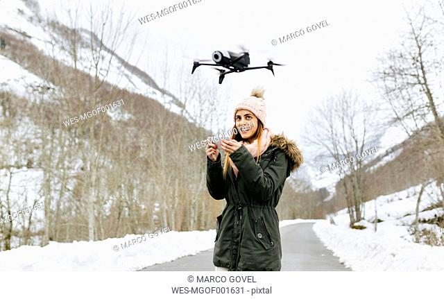 Spain, Asturias, young woman navigating a drone in the snowy mountains