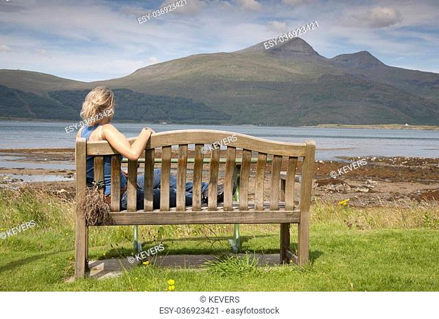 Young Woman sitting on Bench on Isle of Mull; Scotland