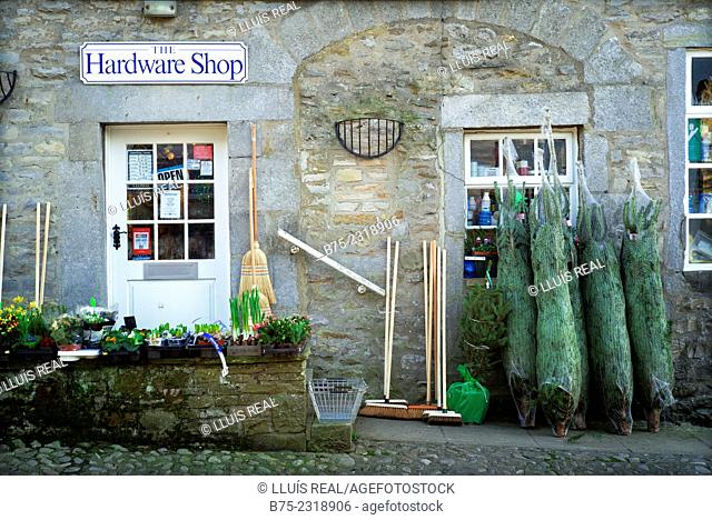 Close up of the front of a hardware store with Christmas trees, brooms and plants, in the village of Grassington. Yorkshire Dales, Englang, UK, Europe