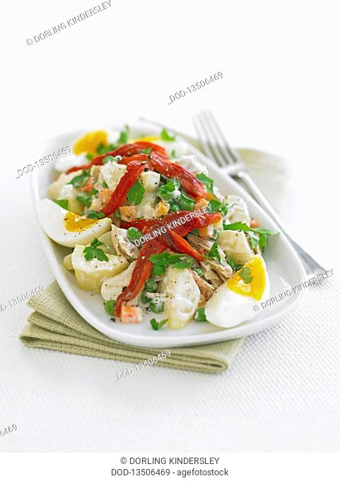 Plate of ensaladilla potato salad with boiled eggs on white background, close-up
