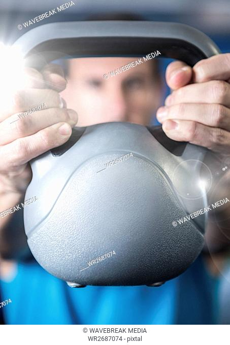 Fitness man holding kettle bell with flare in front of him