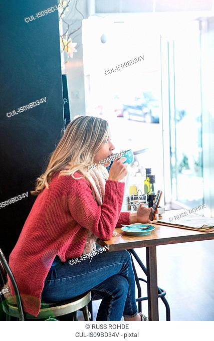 Woman sitting in cafe, drinking coffee, holding smartphone