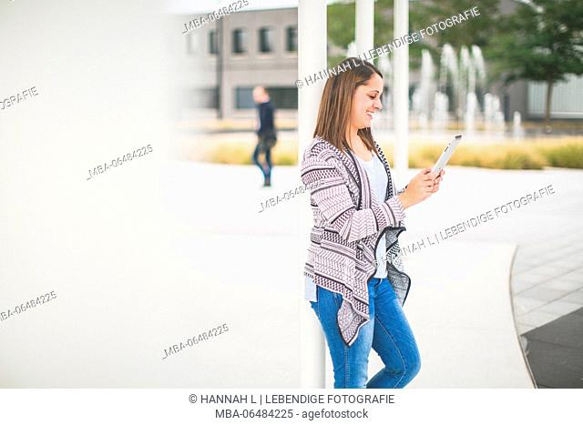 Young woman with tablet computer on the way