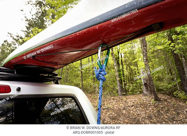Detail of a kayak secured to a vehicle roof at the Cedar Creek Landing area of Congaree National Park in South Carolina. A carabiner and rope secure the kayak...