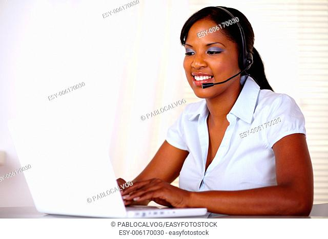 Charming young secretary working on laptop and speaking on microphone - copyspace