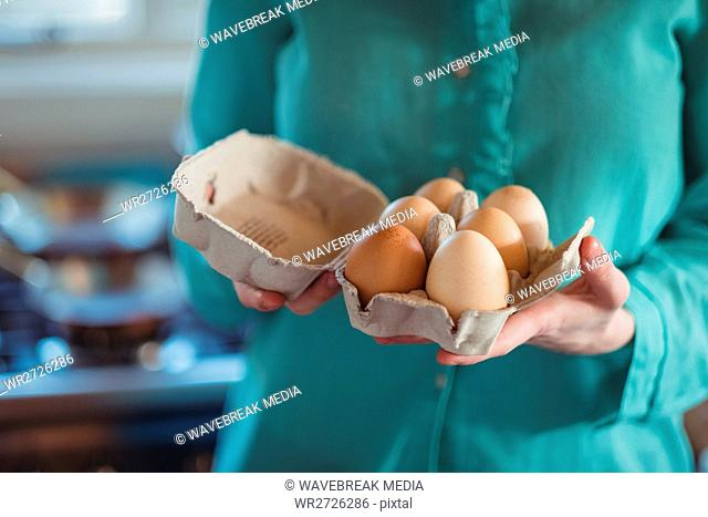 Mid section of woman holding eggs