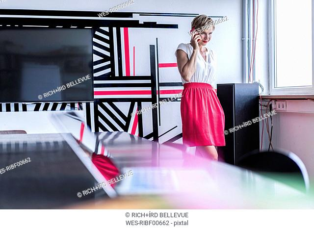 Woman in modern office on cell phone
