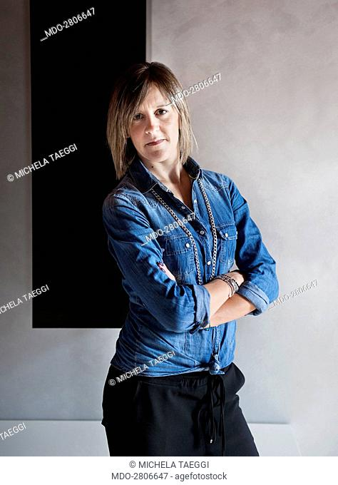 A woman posing with folded arms for the photocall. Caprino Bergamasco (Italy), 15th October 2014