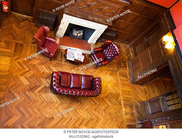 Looking down on hotel soft chairs and sofa with log fireplace and parquet flooring