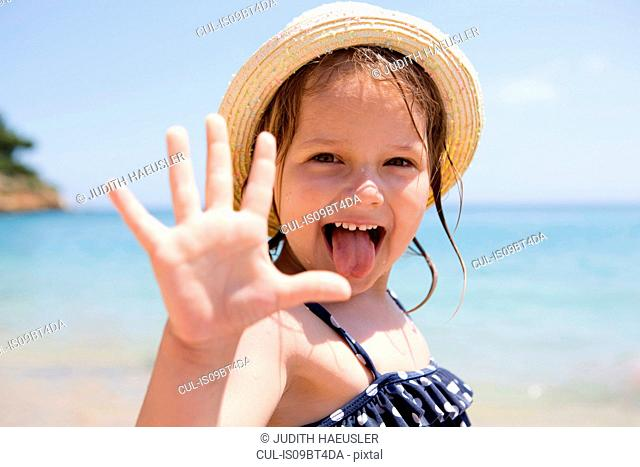 Girl in sunhat sticking out her tongue, portrait, Scopello, Sicily, Italy