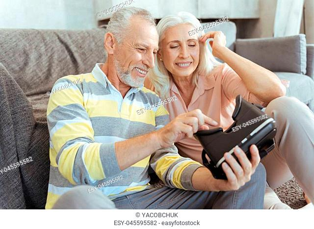 Do you see it. Cheerful smiling retired couple resting at home together and trying up virtual reality glasses
